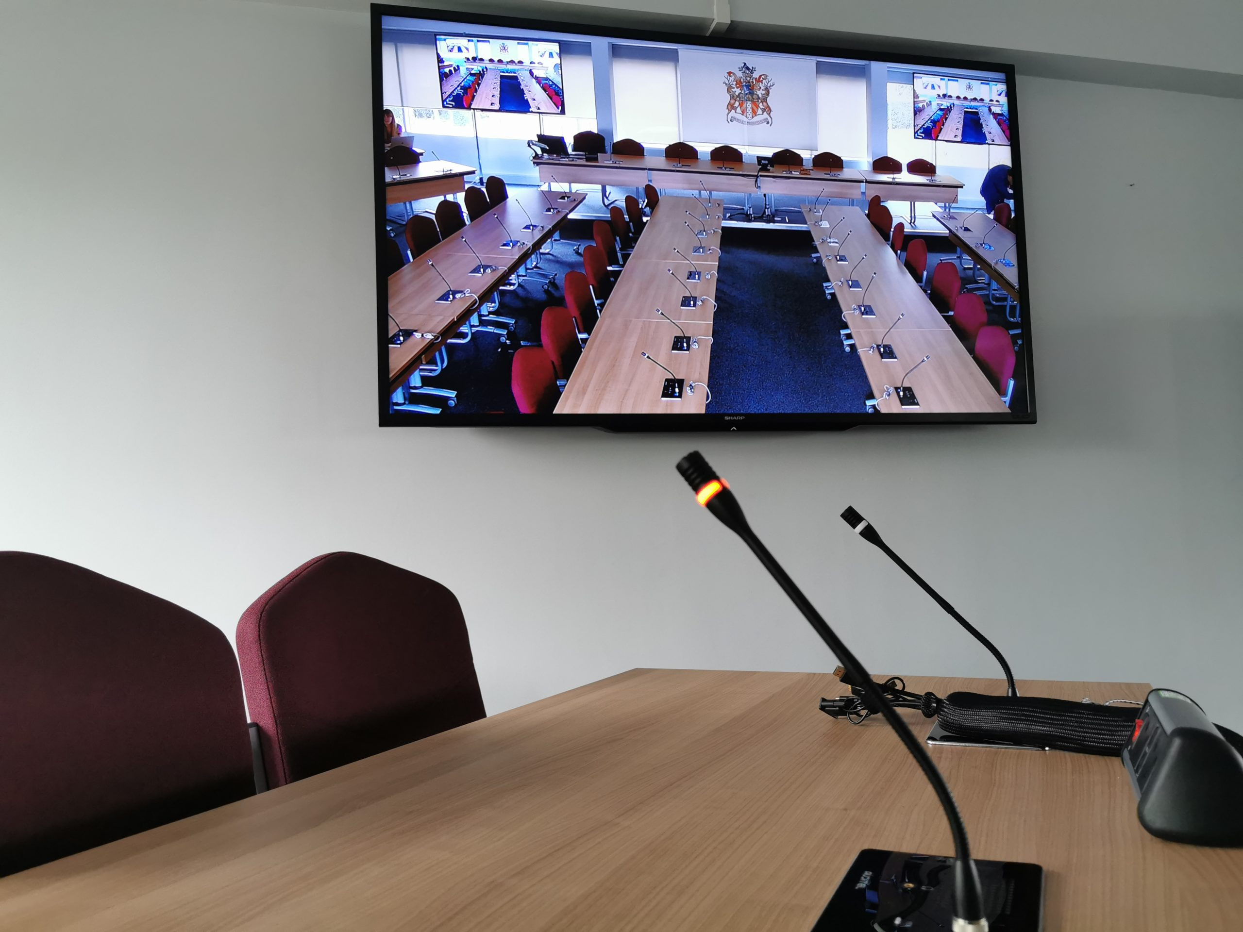 conference microphones and tv screen with live broadcast